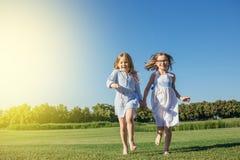 Twee meisjes die op het gebied lopen Stock Foto's