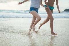 Twee Meisjes die op het Strand lopen stock foto's