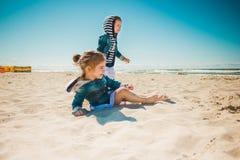 Twee meisjes die op het strand spelen Stock Afbeelding