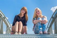 Twee meisjes die op metaal zitten overbruggen met blauwe hemel royalty-vrije stock afbeeldingen