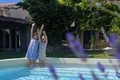 Twee meisjes die op pool paddelen royalty-vrije stock afbeelding