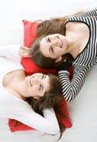 Twee meisjes die op rood hoofdkussen liggen Stock Fotografie