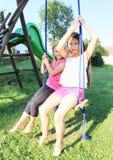 Twee meisjes die op schommeling slingeren Stock Foto