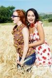 Twee meisjes die op tarwegebied lachen Royalty-vrije Stock Afbeeldingen