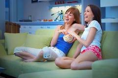 Twee meisjes die op TV letten Stock Afbeeldingen