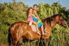 Twee meisjes die paard in de zomer in Ada Bojana, Monte berijden Royalty-vrije Stock Afbeeldingen