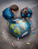 Twee meisjes die realistisch Aardebeeld met krijt trekken op grond Stock Foto