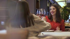 Twee meisjes die in restaurant zitten, en tijdens het nemen van delisious schotelsmier babbelen glimlachen drinken wijn op lunch  stock videobeelden