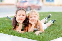 Twee meisjes die in rolschaatsen op het gras leggen Royalty-vrije Stock Afbeelding