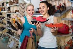 Twee meisjes die schoenen in de opslag kiezen Stock Afbeeldingen