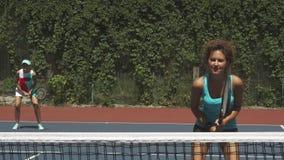 Twee meisjes die tennis in het paar spelen royalty-vrije stock afbeeldingen