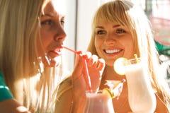 Twee meisjes die van cocktails genieten Stock Afbeeldingen