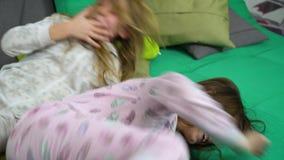 Twee meisjes die voor pret op bank vechten stock footage