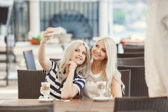 Twee meisjes drinken koffie en gebruiken de telefoon Stock Fotografie