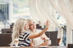 Twee meisjes drinken koffie en gebruiken de telefoon Royalty-vrije Stock Foto's