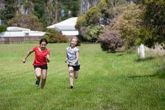 Twee meisjes in dwarsland rennen Stock Afbeelding