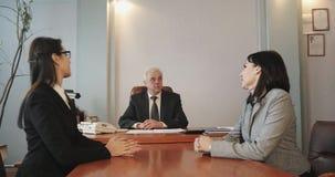 Twee meisjes in een gesprek met de directeur van het bedrijf stock footage