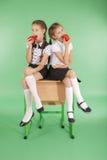 Twee meisjes in een school eenvormige zitting op bureau en eten appelen Stock Afbeeldingen