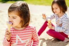 Twee meisjes eet roomijs terwijl het zitten op de speelplaats Stock Foto's