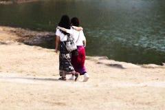 Twee meisjes elkaar houden die lopend in het zand stock afbeeldingen