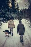 Twee meisjes en een hond lopen in het de winterbos stock afbeelding