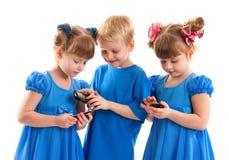 Twee meisjes en een jongen met hun celtelefoons Royalty-vrije Stock Foto's