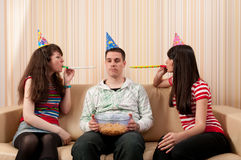 Twee meisjes en een kerel die een verjaardagspartij heeft Stock Foto