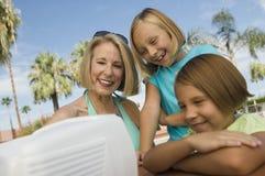 Twee meisjes (7-9) en grootmoeder die op draagbare televisie in openlucht letten. stock foto