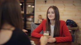 Twee meisjes in en koffie die glimlachen spreken stock videobeelden