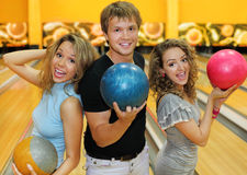Twee meisjes en mens houden ballen in kegelenclub Royalty-vrije Stock Foto's