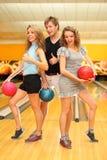 Twee meisjes en mens houden ballen in kegelenclub Stock Afbeelding
