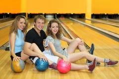 Twee meisjes en mens zitten op vloer in kegelenclub Royalty-vrije Stock Afbeeldingen