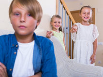 Twee meisjes en nukkige jongenszitting die afzonderlijk thuis spreken Royalty-vrije Stock Afbeeldingen