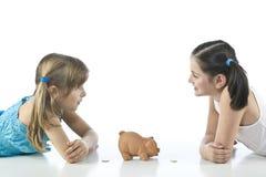 Twee meisjes en spaarvarken Stock Fotografie
