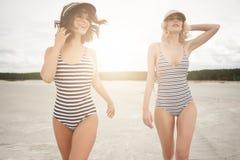 Twee meisjes gaan in het avond strand Stock Foto