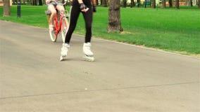 Twee meisjes gaan het rollerblading en fiets stock video