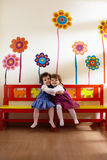 Twee meisjes glimlachen en omhelzing op school royalty-vrije stock afbeelding