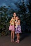 Twee meisjes in het bos bij nacht Stock Afbeelding