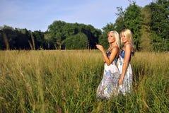 Twee meisjes in het gras dichtbij het bos Royalty-vrije Stock Afbeelding