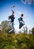 Twee meisjes hoog opgewekt springen Stock Fotografie