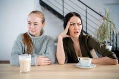 Twee meisjes jonge vrouwen die in een koffie met koffiekoppen zitten, die tegenover richting kijken royalty-vrije stock foto