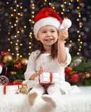 Twee meisjes in Kerstmisdecoratie met gift, donkere achtergrond met verlichting en boke lichten, het concept van de de wintervaka Royalty-vrije Stock Foto's