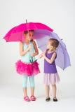 Twee meisjes in kleurrijke robes met paraplu's stock afbeelding