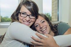 Twee meisjes koesteren elkaar Stock Foto
