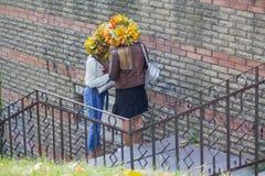 Twee meisjes in kronen van gele bladeren in de stad parkeren stock foto