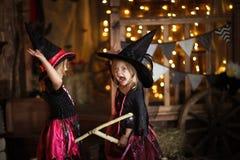 Twee meisjes lachende heks op een bezemsteel kinderjaren Hallo stock afbeeldingen