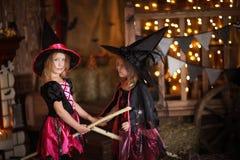 Twee meisjes lachende heks op een bezemsteel kinderjaren Hallo stock fotografie
