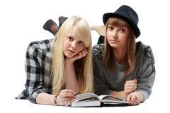 Twee meisjes ligt en lezen boeken Stock Foto