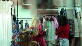 Twee meisjes lopen in een kledingsopslag, bekijken zij kleren en proberen het stock video