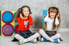 Twee meisjes luisteren aan muziek op hoofdtelefoons Conceptenmuziek, r Stock Fotografie